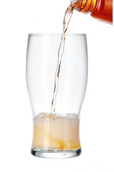 Bier het gieten van fles in glas op wit wordt geïsoleerd dat