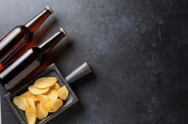 Bier in donkere glazen flessen en zoute snacks.