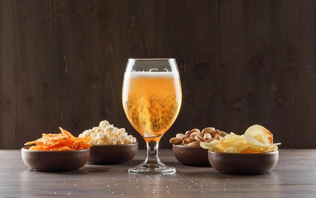 Bier in een drinkbeker glas met junk food zijaanzicht op een houten tafel