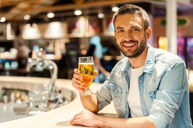 Bier tijd. vrolijke jonge man die een glas bier vasthoudt en naar de camera kijkt terwijl hij aan de bar zit