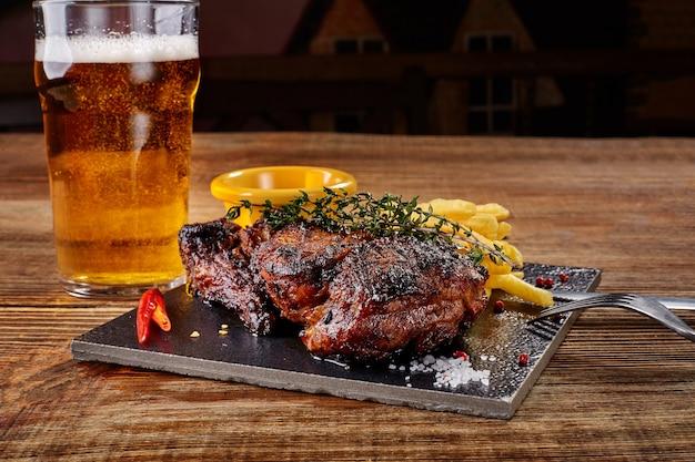 Bier wordt gegoten in glas met gastronomische biefstuk en frietjes op houten achtergrond
