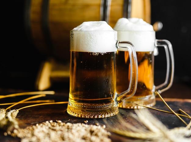 Bierglazen en tarwekruid op een oude rustieke houten lijst aangaande zwarte achtergrond