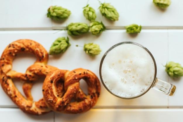Bierpul, hopbellen en pretzels op een witte houten tafel.
