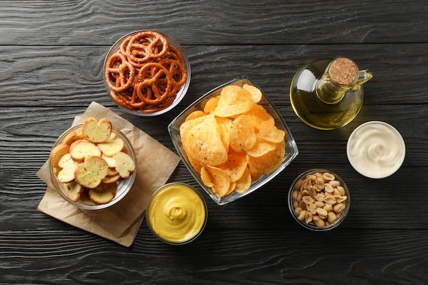 Biersnacks, chips, biernoten, sauzen, olijfolie op houten, ruimte voor tekst. bovenaanzicht