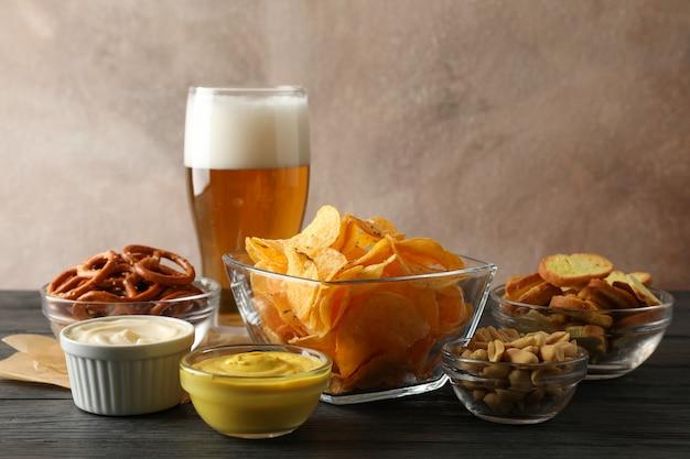 Biersnacks, glas bier, chips, biernoten, sauzen, glas bier op hout, ruimte voor tekst