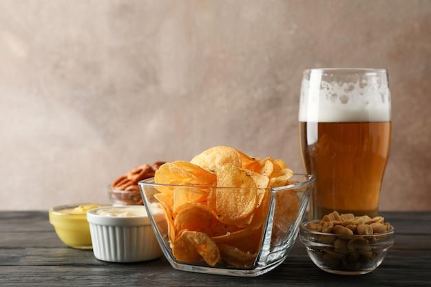 Biersnacks, glas bier, chips, biernoten, sauzen, glas bier op houten, ruimte voor tekst