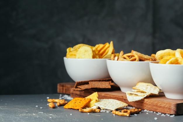 Biersnacks op stenen tafel. verschillende crackers, chips. bovenaanzicht