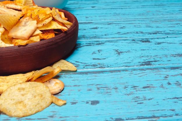 Biersnacks zoals crackers, chips, koekjes op een houten oppervlak