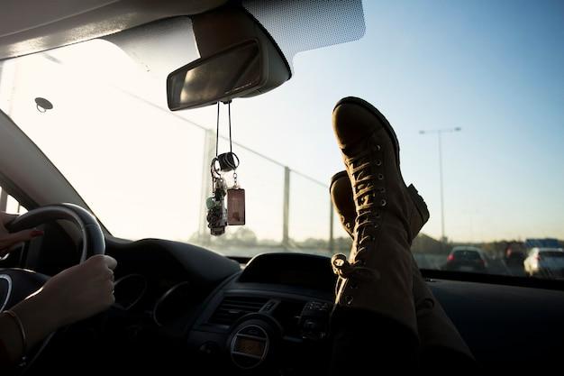 Bies de benen in de buurt van de voorruit in de auto