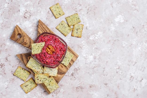 Bietenhummus op snijplank met zoute koekjes op lichte oppervlakte