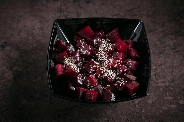 Bietensalade op donkere ondergrond. gekookte bieten, olie en sesamzaadjes in zwarte kom