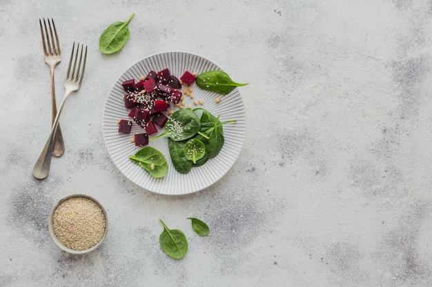 Bietensalade op lichte ondergrond. gekookte bieten, babyspinazieblaadjes en sesamzaadjes in witte plaat
