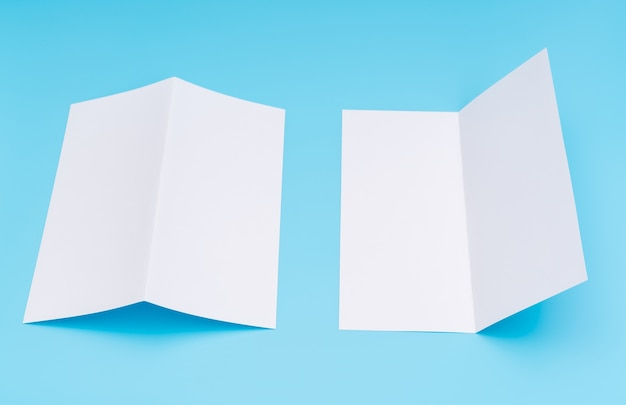 Bifold wit sjabloon papier op blauwe achtergrond.