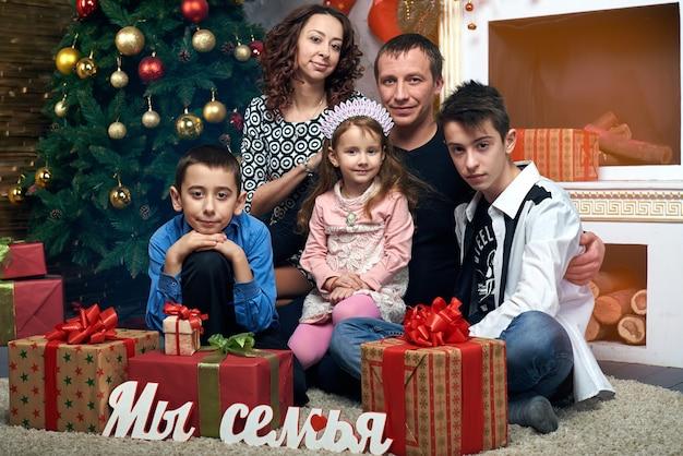 Bij de boom bij de open haard en gelukkige familie. moeder, vader en drie kinderen op wintervakantie. kerstavond en oudejaarsavond.
