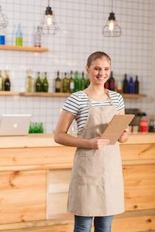 Bij de cafetaria. vrolijke aardige positieve vrouw die een schort draagt en notities vasthoudt tijdens het werken in de cafetaria