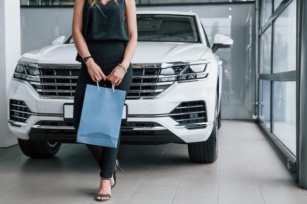 Bij de deuren. meisje en moderne auto in de salon. overdag binnenshuis. een nieuw voertuig kopen