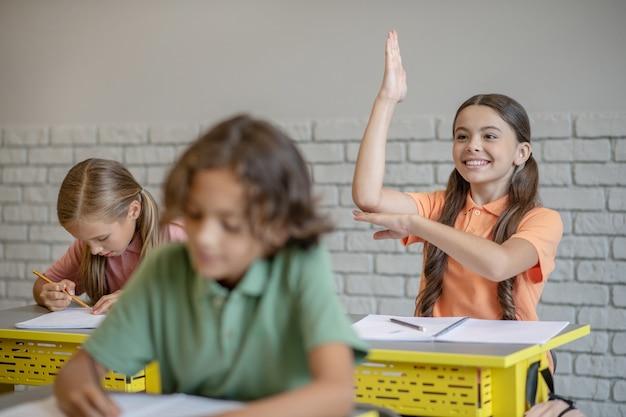 Bij de les. donkerharig meisje dat haar hand opheft klaar om te antwoorden