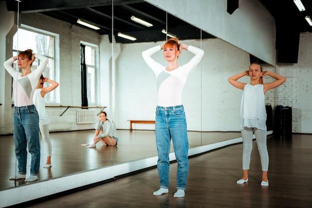 Bij de spiegel. roodharige balletleraar en haar student kijken betrokken tijdens het dansen in de buurt van de spiegel
