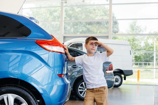 Bij een autodealer staat een gelukkige jongen bij een nieuwe auto voordat hij hem koopt. aankoop van een auto.