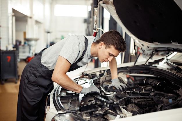 Bij een autoservice: een gediplomeerde monteur heeft te maken met een automotor.