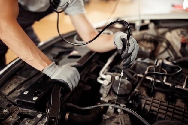 Bij een autoservice: een monteur zoekt naar bugs.