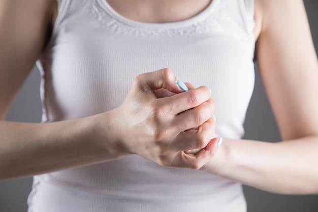 Bij een jonge vrouw doen vingers pijn aan een grijze muur