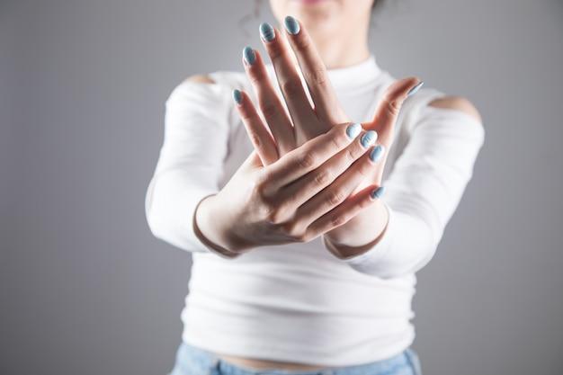 Bij een jonge vrouw doen vingers pijn in een grijze scène