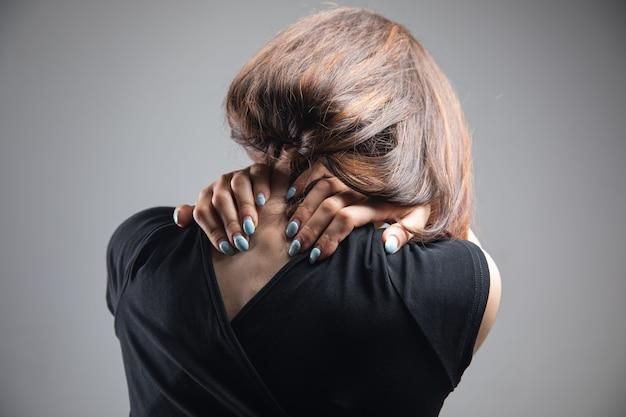 Bij een jonge vrouw doet de achterkant van haar hoofd pijn op een grijze achtergrond