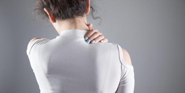 Bij een jonge vrouw doet de achterkant van haar hoofd pijn op een grijze scène