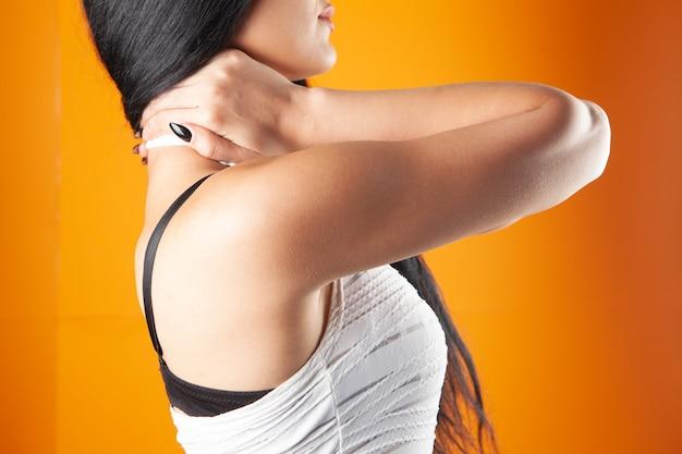 Bij een jonge vrouw doet de achterkant van haar hoofd pijn op een oranje achtergrond