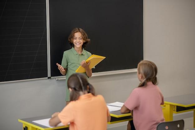 Bij het bord. een jongen in groene t-shirt die zich bij het bord bevindt
