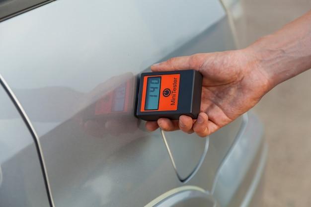 Bij het controleren van de carrosserie en deuren van de auto meet de man de carrosserie van de auto met het apparaat