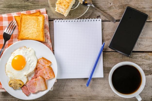 Bij het ontbijt aan mijn plannen denken. gebakken ei en spek, concept achtergrond