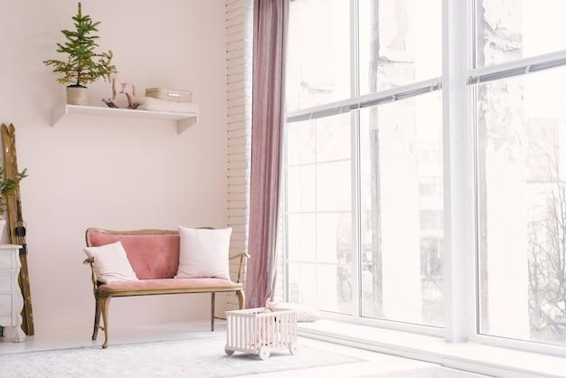 Bij het raam in de woonkamer of kinderkamer staat een roze vintage bank met kussens