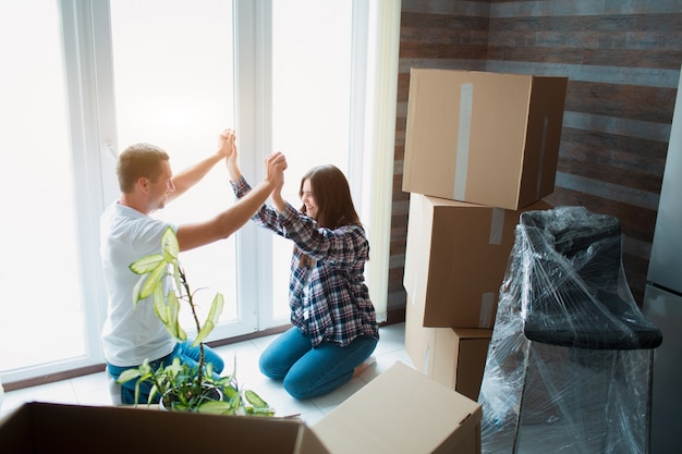 Bij het raam zit een jong getrouwd stel in de woonkamer van het huis. hey zijn blij met een nieuw huis. verhuizen, een huis kopen, appartementenconcept.
