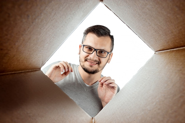Bij het uitpakken opent een man de doos en kijkt naar binnen
