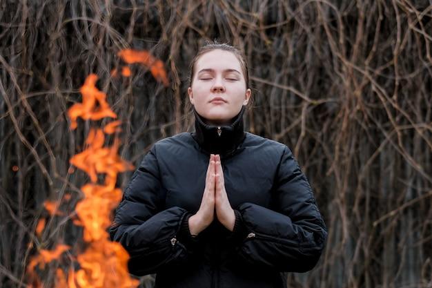 Bij het vuur staat een meisje met gevouwen handen in gebed en gesloten ogen