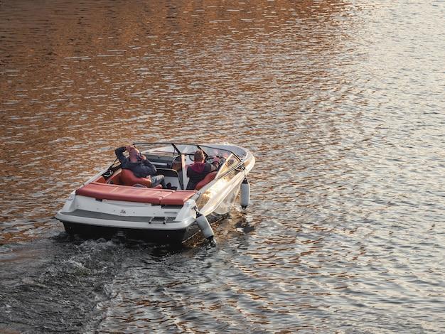Bij zonsondergang staat een luxe motorboot op het water. ontspan in een motorboot. moskou.