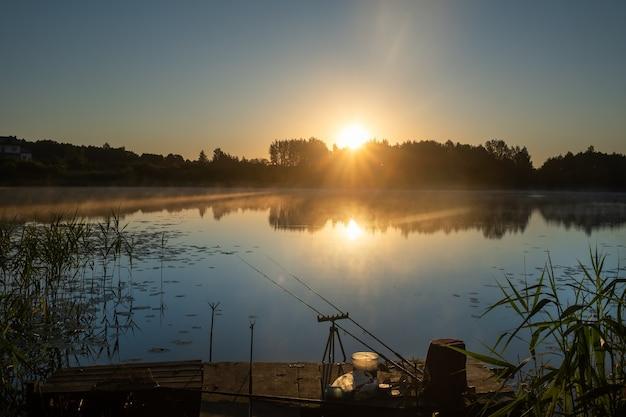 Bij zonsopgang worden twee hengels op de pier geïnstalleerd om vis op het meer te vangen