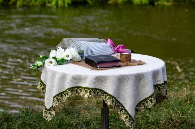 Bijbel, een kaars en een boeket bloemen staan op de tafel tegen de rivier.