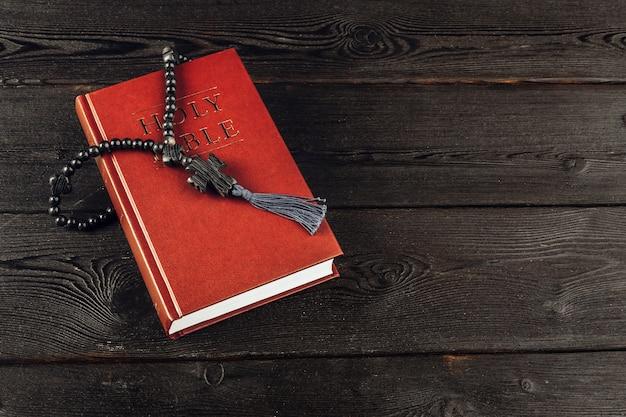 Bijbel en een kruisbeeld op een oude houten tafel. religie concept.