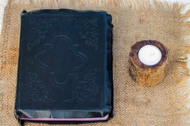 Bijbel en kaars op een juteservet.