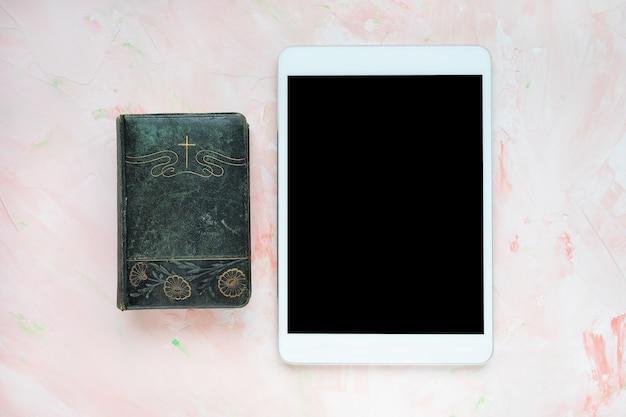 Bijbel en tablet op roze christelijke achtergrond
