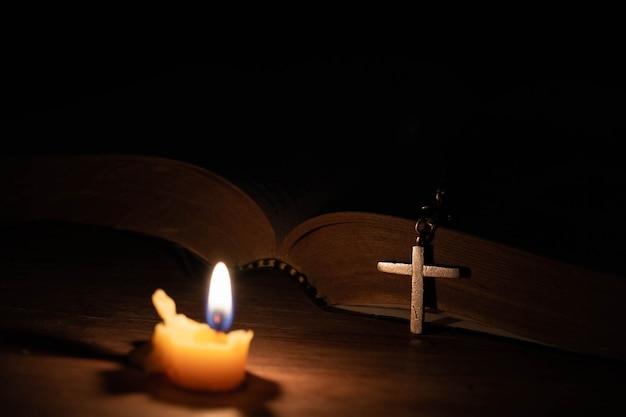 Bijbel, houten kruis en kaarsen