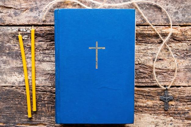 Bijbel, kruis en kaarsen voor huisgebed op een houten achtergrond