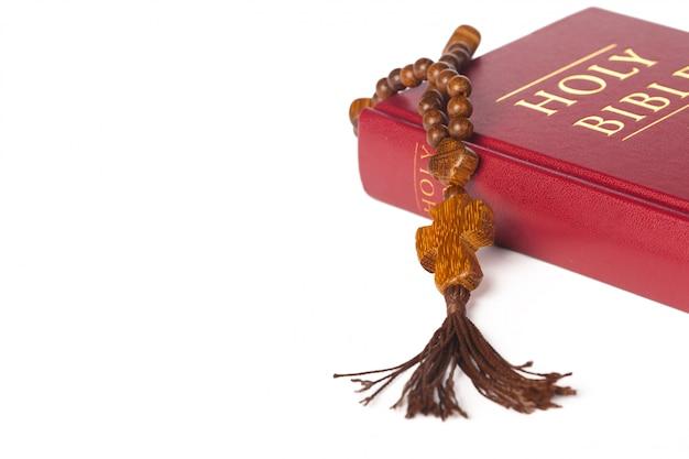 Bijbel op een witte achtergrond. heilig boek en houten rozenkrans.