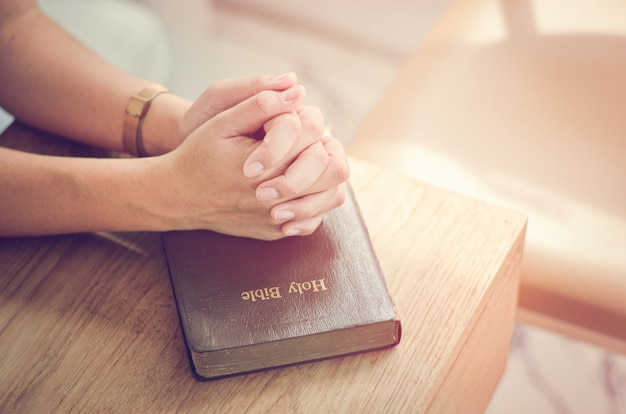 Bijbelgebed vouw je handen in de bijbel bid spiritueel en religieus communiceer met god, liefde en vergeving.
