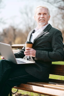 Bijeenkomst in park. lage hoek van reflecterende volwassen zakenman met behulp van laptop terwijl die zich voordeed op de bank