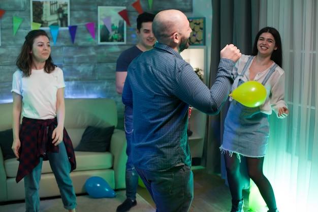 Bijeenkomst van jonge mensen die dansen in een appartement om hun vriendschap te vieren.