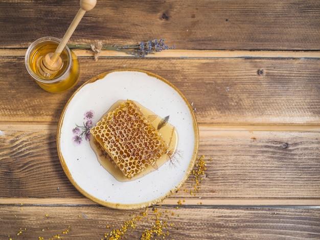 Bijenpollen; honingpot en honingraat stuk op witte plaat over de tafel
